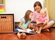 Eine Frau liest zwei Kindern vor