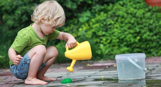 Kleines Kind spielt mit Gießkanne