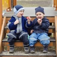 Zwei Kinder sitzen auf einer Treppe und essen Äpfel